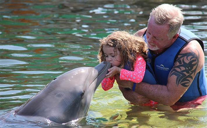 Man holding his daughter as she gives a dolphin a kiss