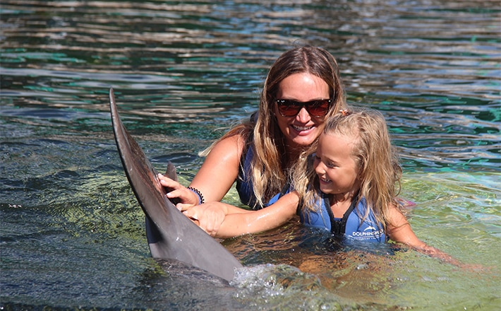 Woman with her daughter while they touch a dolphin