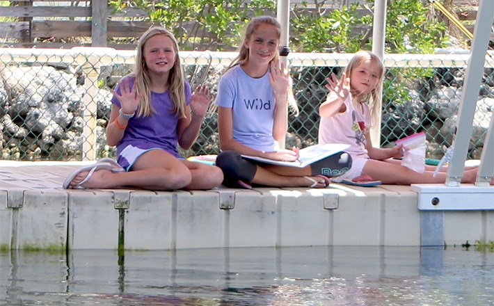 Three girls taking notes on the dock