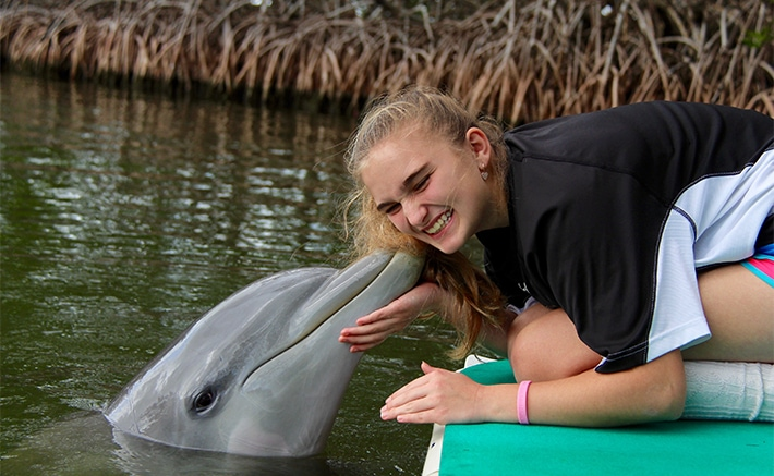 Girl getting kissed by a dolphin