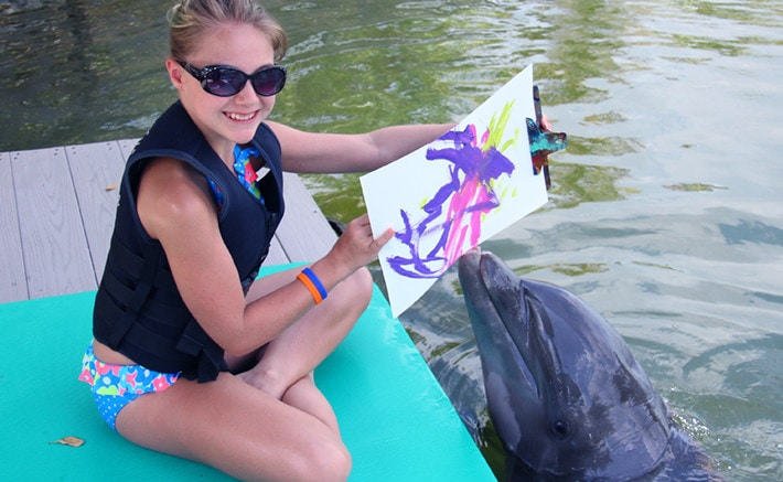 Girl holding up a painting by a dolphin while dockside