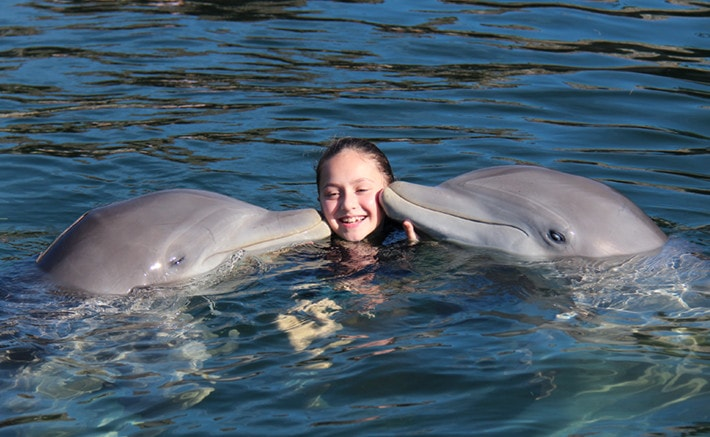 Girl being kissed by two dolphins while in the water