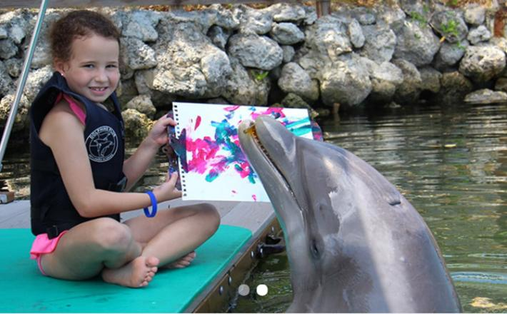Girl holding up her dolphin painting